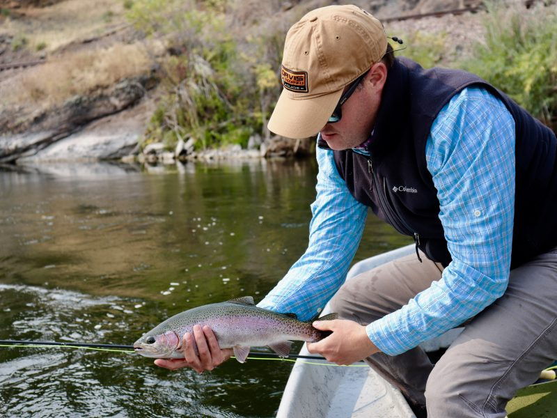 Man releasing trout from boat into river